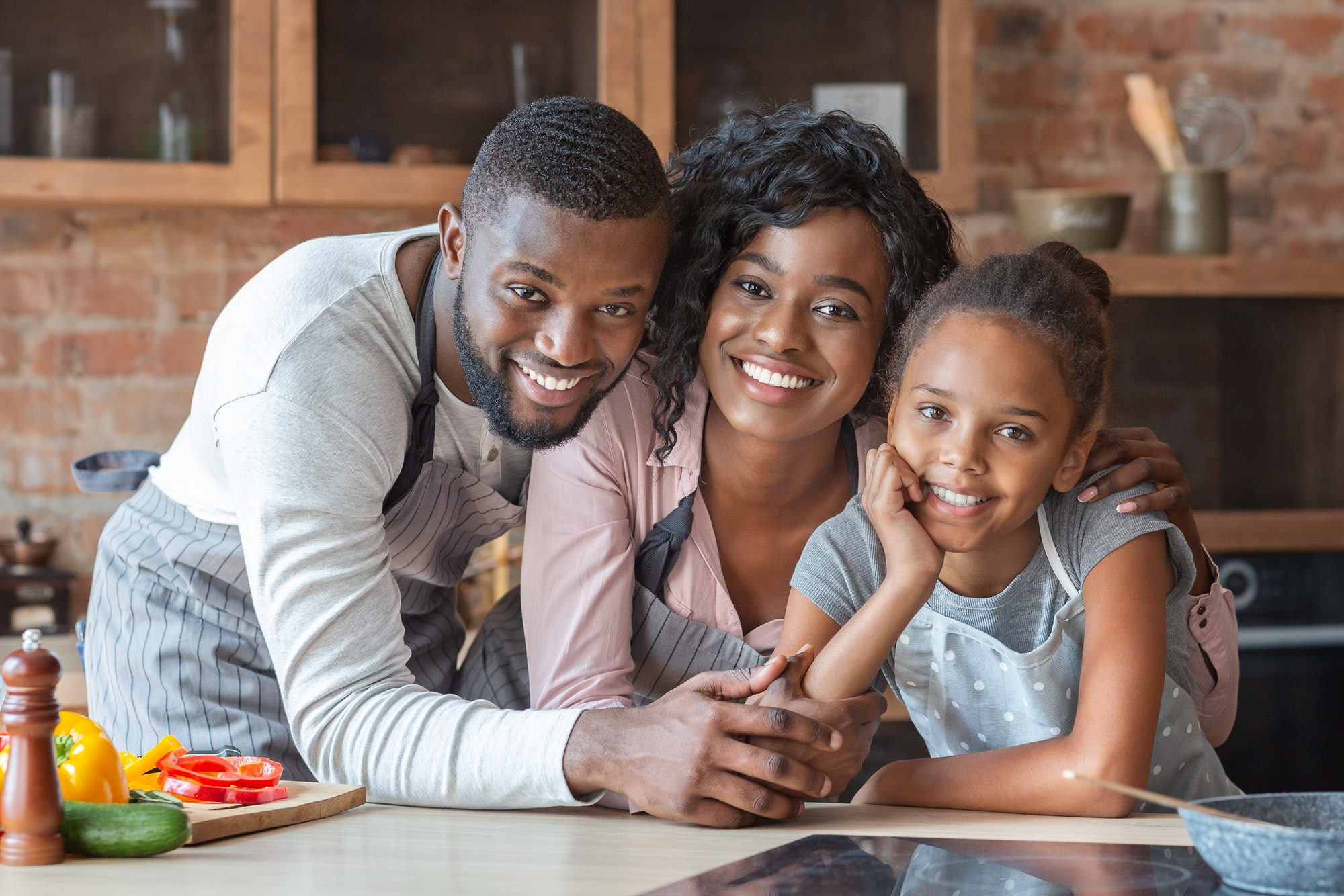 Cheerful african family spending time together at kitchen