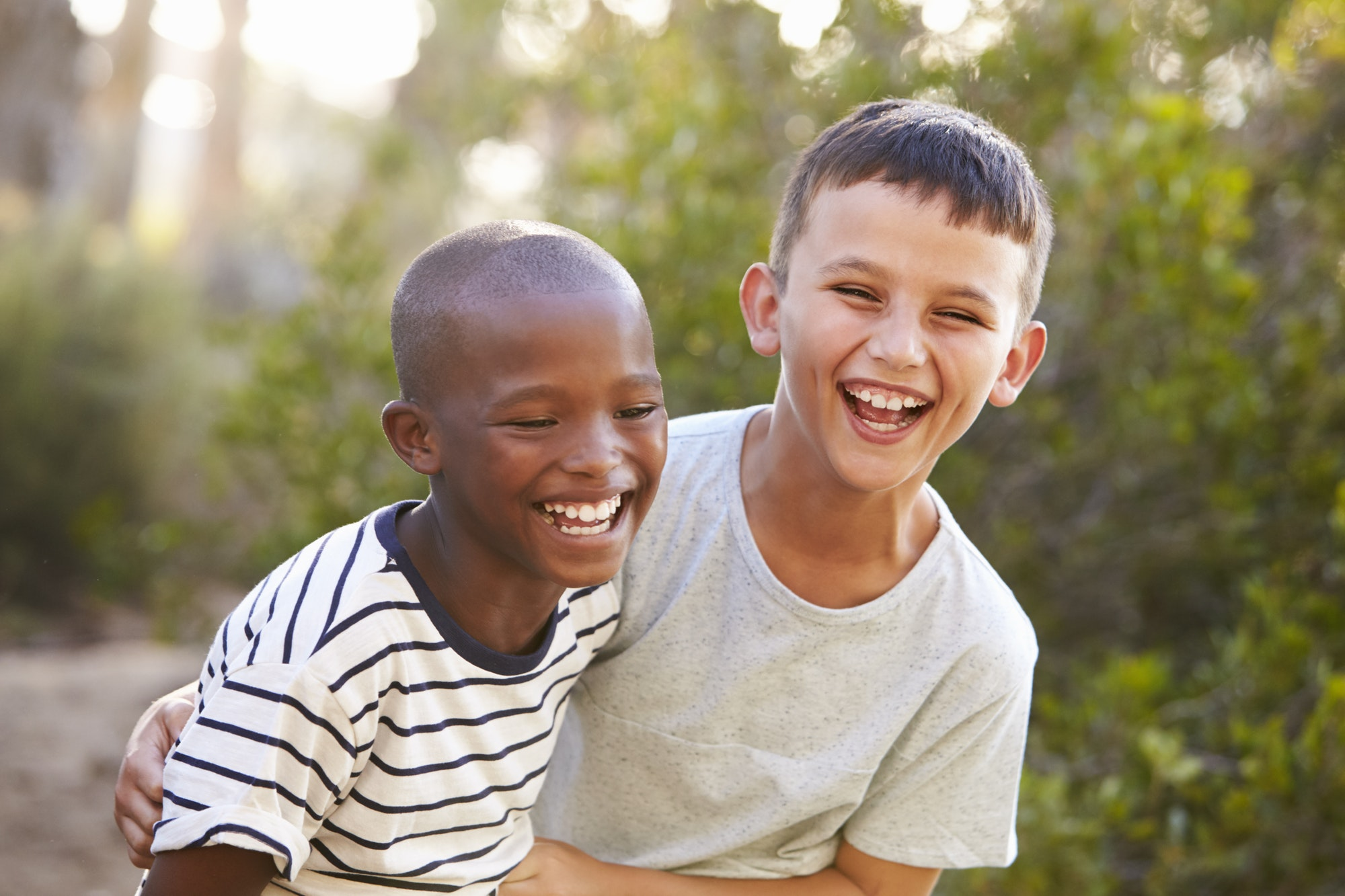 Portrait of two boys embracing and laughing hard outdoors