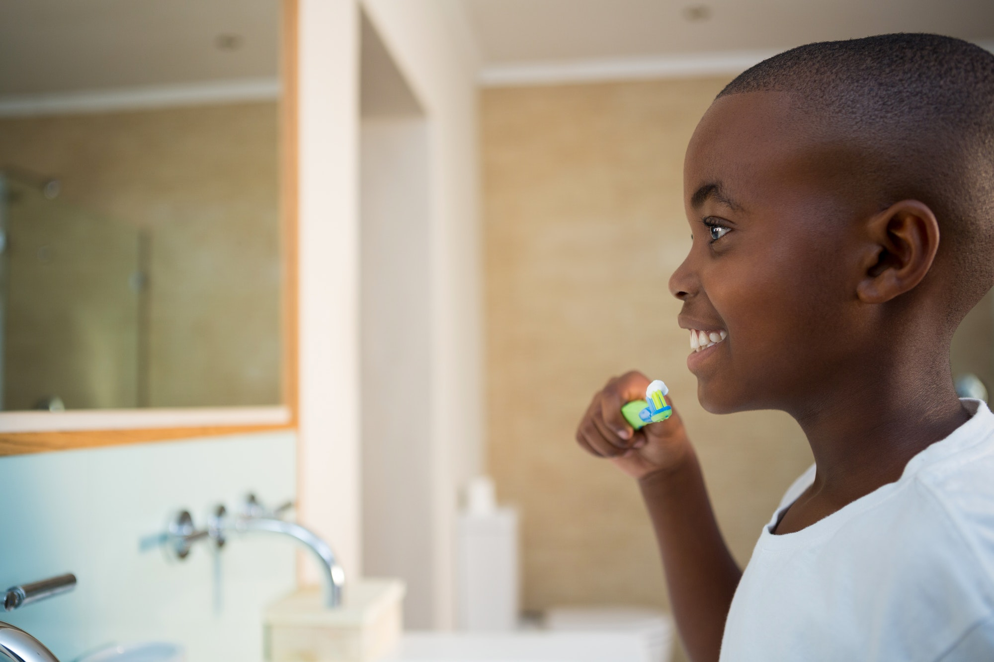 Side view of smiling boy with toothbrush